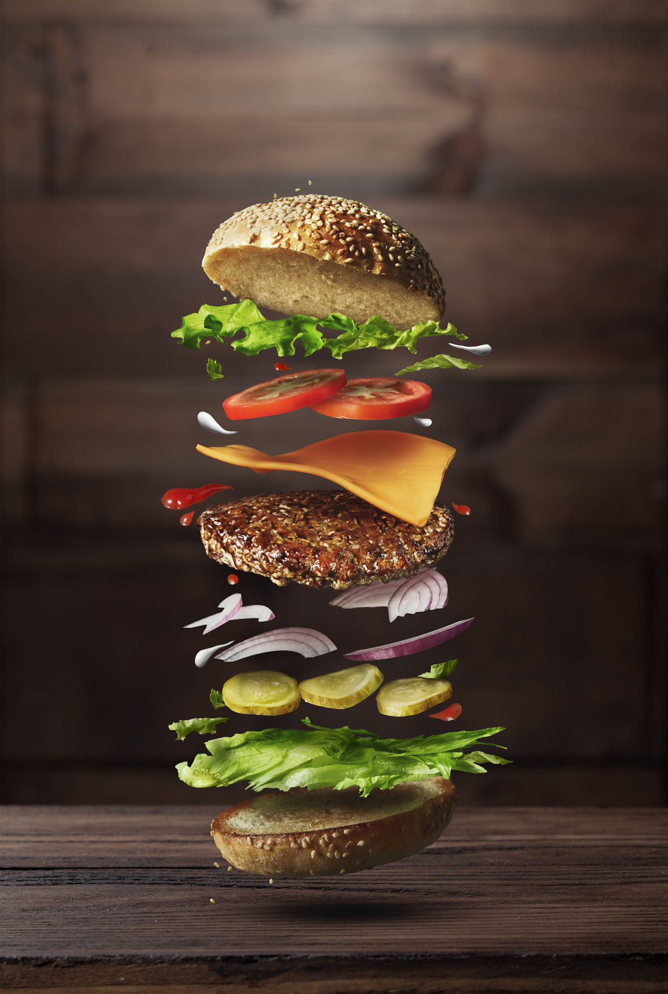 Classic burger ingredients flying on a wooden brown background ...