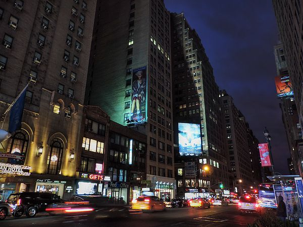 Cars and yellow cabs run south down 7th Ave., better known as Fashion Ave., under the deep blue of twilight in Midtown Manhattan, NYC.