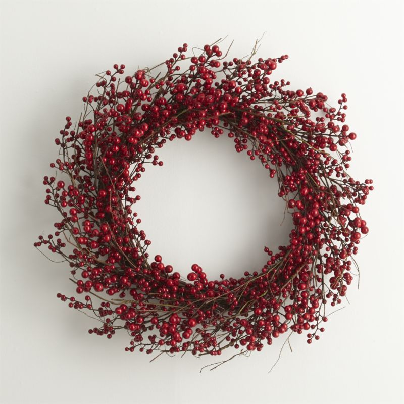 Twigs Of Faux Berries Wind A Large Wreath Adding Festive Color Above