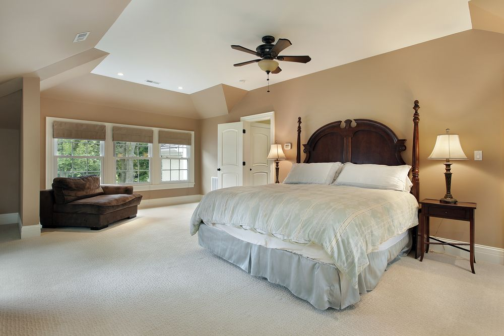 Sand Colored Walls Lead To Vaulted Ceiling In This Minimal Bedroom Featuring Large Polished Dark Wood Bed Frame With Light Bedding Brown Reading Chair