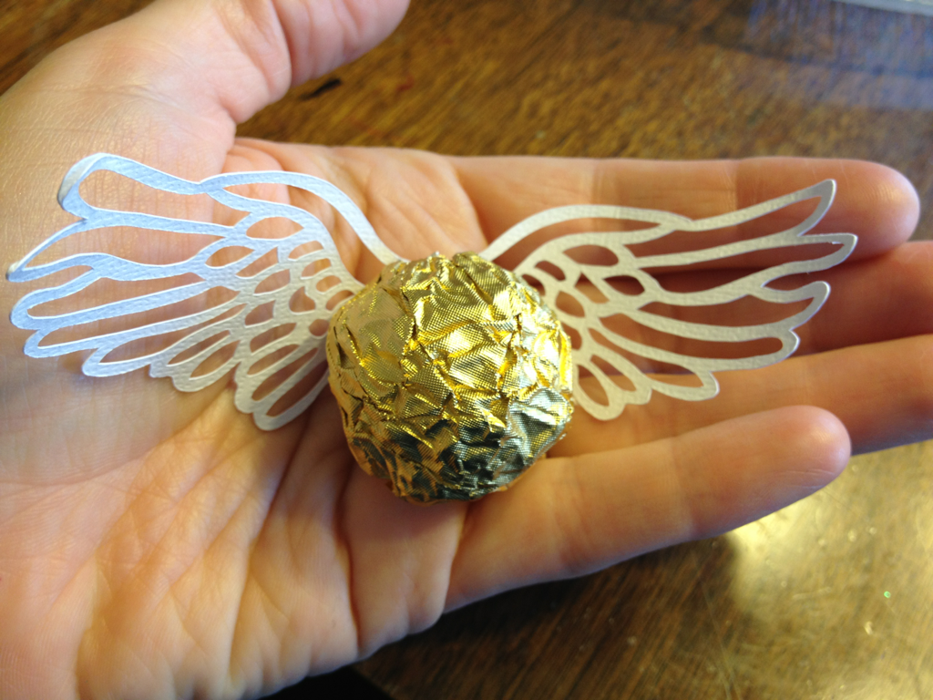 Little golden snitches! aka ferrero rocher with wings. I cut the wings on my Silhouette Cameo, the Rolls Royce of paper cutting machines. Little dab o' glue, and done.