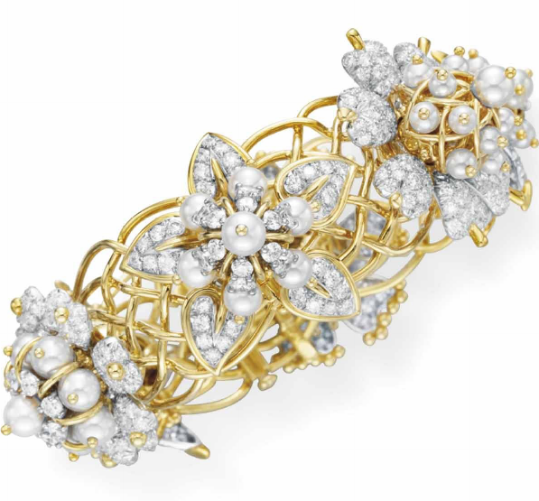 A DIAMOND, CULTURED PEARL AND GOLD BRACELET, BY JEAN SCHLUMBERGER, TIFFANY & CO. The hinged bracelet set with a series of six variously-designed circular-cut diamond and cultured pearl flower blossoms, to the sculpted 18k gold openwork band, mounted in 18k gold and platinum, 2½ ins. diameter, in a Tiffany & Co. black leather case Signed Schlumberger Studios for Jean Schlumberger, Tiffany & Co., no. 23777304