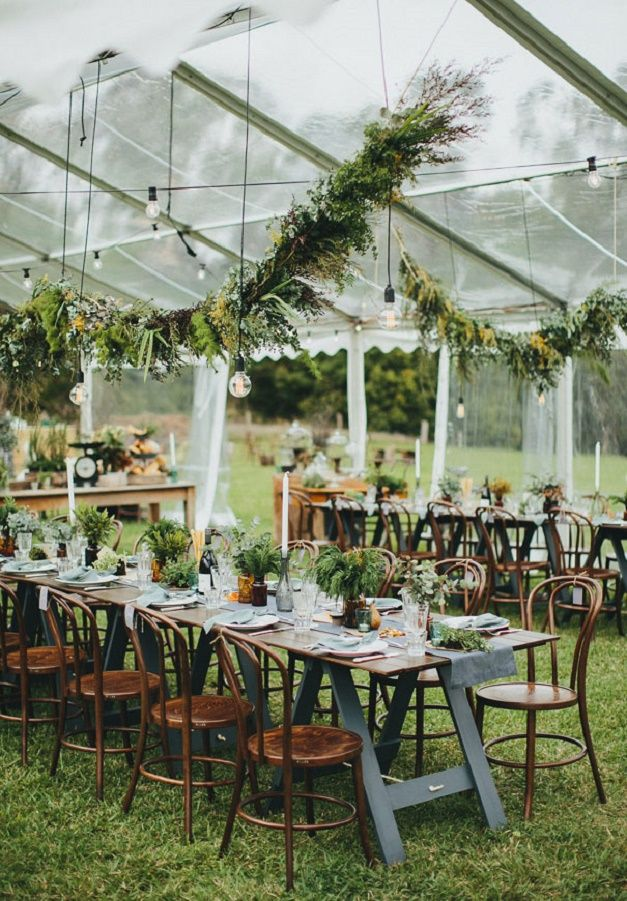 Wedding reception under marquee decorated garland and hanging light bulbs