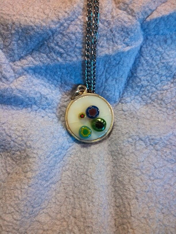 White glass cab with multi colored glass filigree accents in brass bezel.original. $35.00