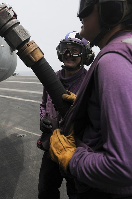 ARABIAN GULF (July 10, 2013) Aviation Boatswain's Mate (Fuel) Airman Mark Bunn, left, and Aviation Boatswain's Mate (Fuel) Melissa Grotenhuis fuel a jet on the flight deck of the aircraft carrier USS Nimitz (CVN 68). Nimitz Strike Group is deployed to the U.S. 5th Fleet area of responsibility conducting maritime security operations, theater security cooperation efforts and support missions for Operation Enduring Freedom.