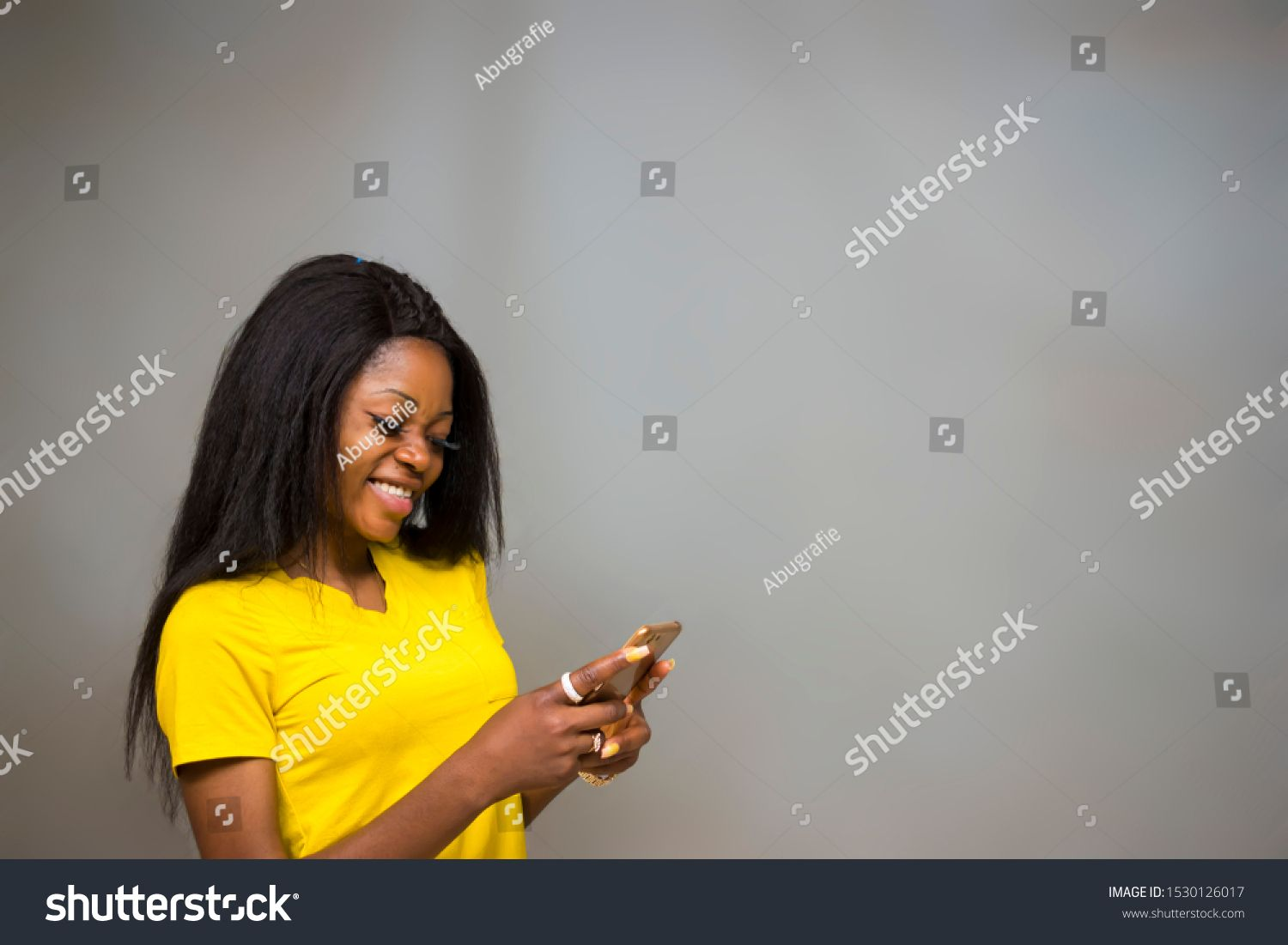 satisfied Young African hipster girltypes text message on cell phone enjoys online communication types feedback wears yellow shirt isolated on Gray studio wall Technology...