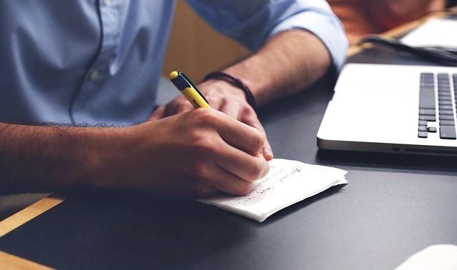 Foto de señor anotando en su escritorio