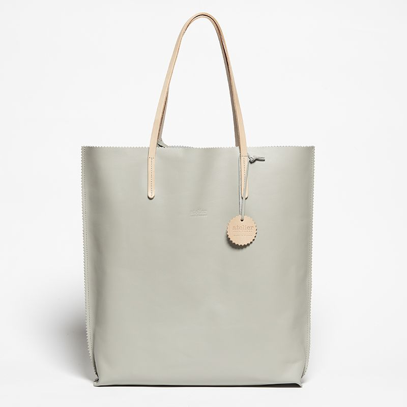 An iconic tote bag from the ATELIER collection, the bag's minimalist design and spacious interior make it the ideal companion to take you from day to night.  -Vegetable leather handles  -Cotton storage pouch Details: removable snap hook and leather badge Capacity: A4 file and 15'' computer