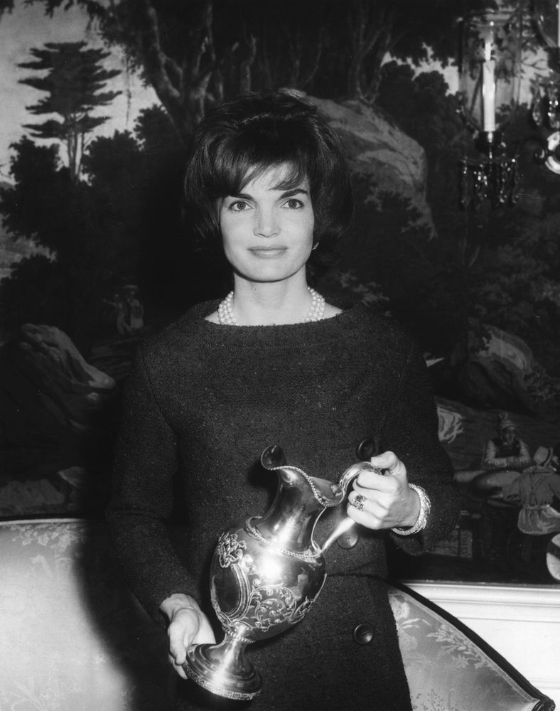 Holding a silver pitcher that was presented to the White House as a diplomatic gift in 1962.