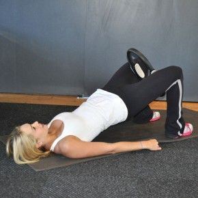 Lie faceup with feet hip-width apart. Place a Pilates ring between thighs. Pressing hands into the floor, engage abs and lift hips toward the ceiling into a bridge position.
