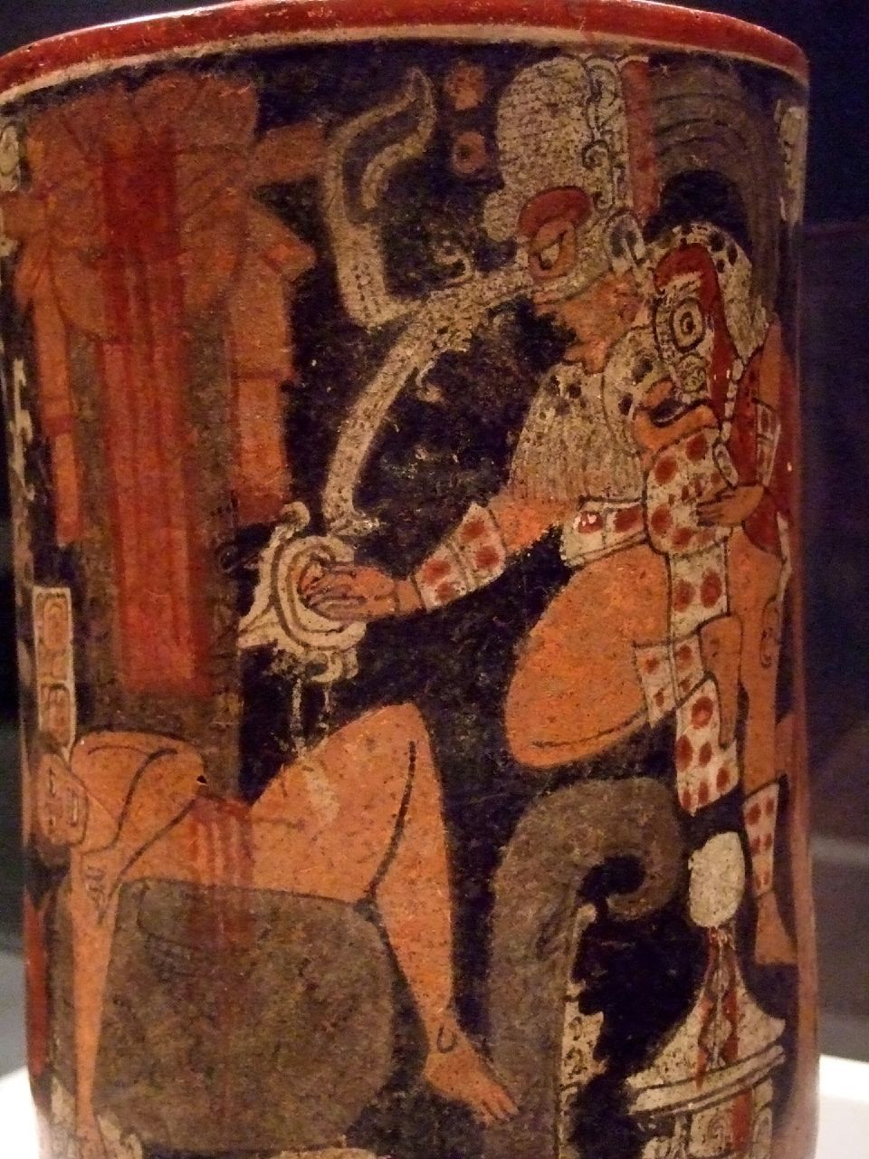 A Maya cylindrical vessel with a scene showing human ...