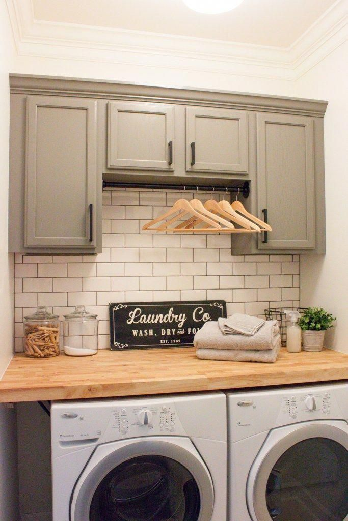 Farmhouse inspired laundry room with modern white subway tile and gray cabinets. Don't forget the bar to