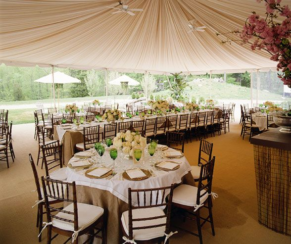 a garden luncheon is held under a tent with three open sides so guests can view