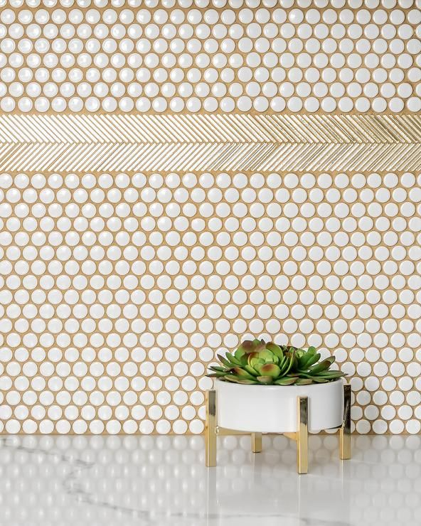 White penny tiles accented with gold grout are ...