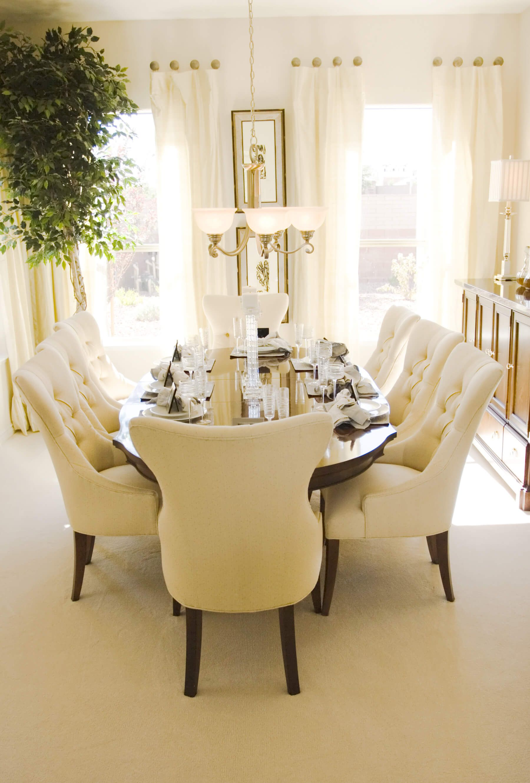 Bright Sunny Dining Room With Oval Wood Table And Eight Plush Cream Colored Chairs
