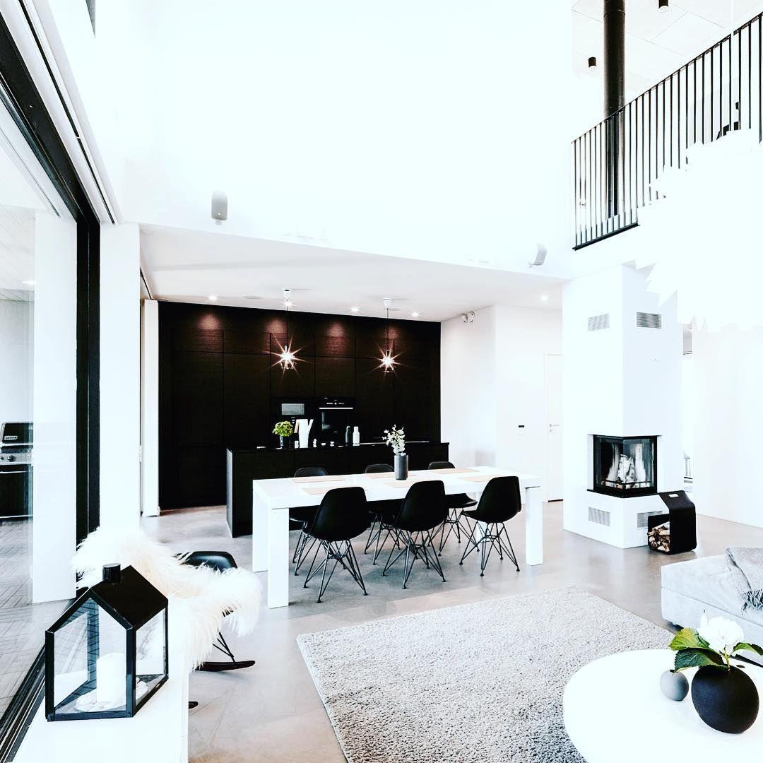 Suuri huonekorkeus ja tasapainoisen mustavalkoinen sisustus luovat ylellistä tunnelmaa. Oleskelutila ja keittiö ruokapöytineen yhdistävät avoimeksi kokonaisuudeksi, jonka kruunaa takka tilan keskellä.