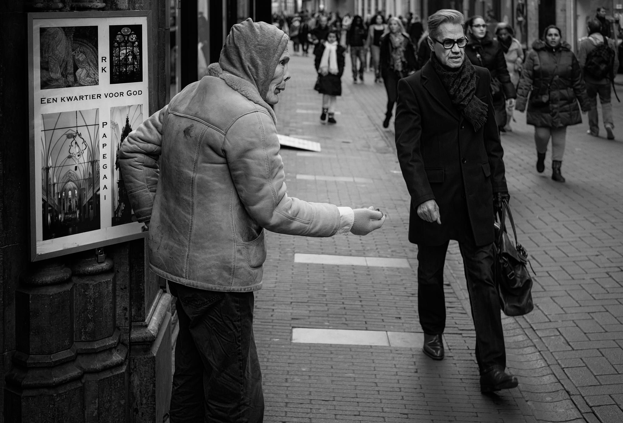 A quarter for God, a dime for me... - Beggar asking for money while standing in…
