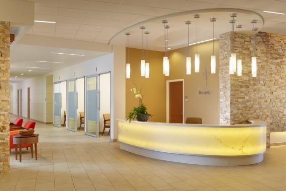 Pendant Lighting And Back Lit Surfaces Serve As Focal Points In The Reception Registration