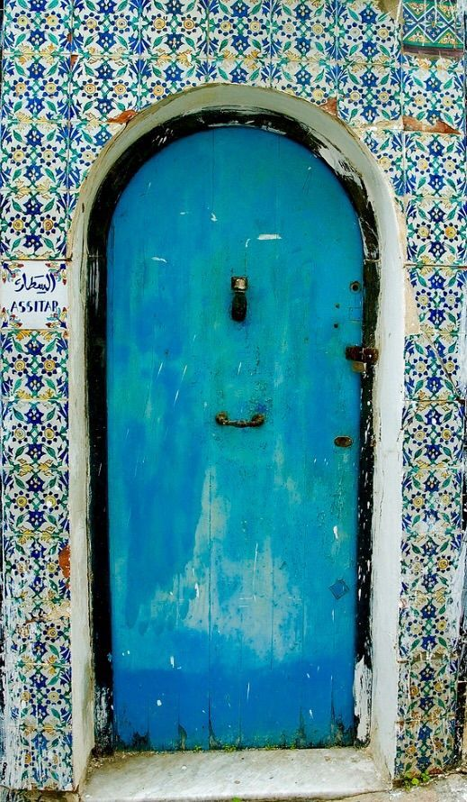 Beautiful turquoise door and tile surround.