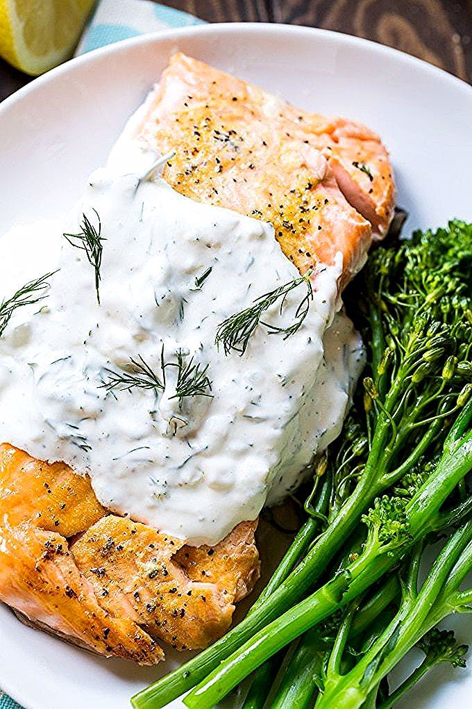 Photo of Salmon is baked in the oven and covered with a creamy dill sauce.
