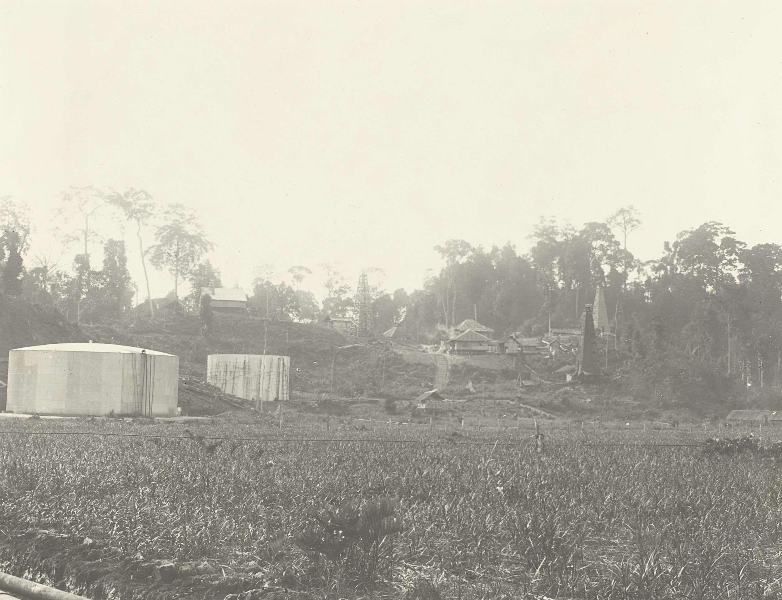 Anonymous | Olietanks en boortoren, Anonymous, 1903 - 1907 | Gezicht op olietanks en een boortoren in een dorp. Foto in het fotoalbum over de oliewinning op Borneo door de Koninklijke Nederlandsche Petroleum Maatschappij (KNPM) in de jaren 1903-1907.