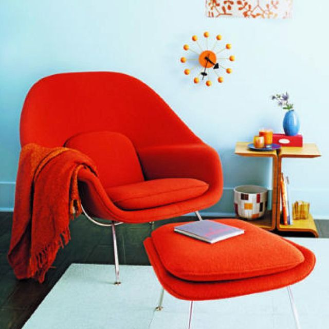 Womb Chair in bright red-orange, with awesome wall clock to boot.