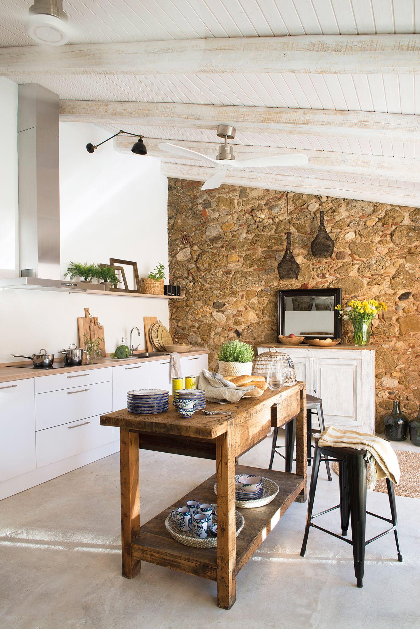 Cocina blanca con pared de piedra, vigas de madera en blanco e isla ...