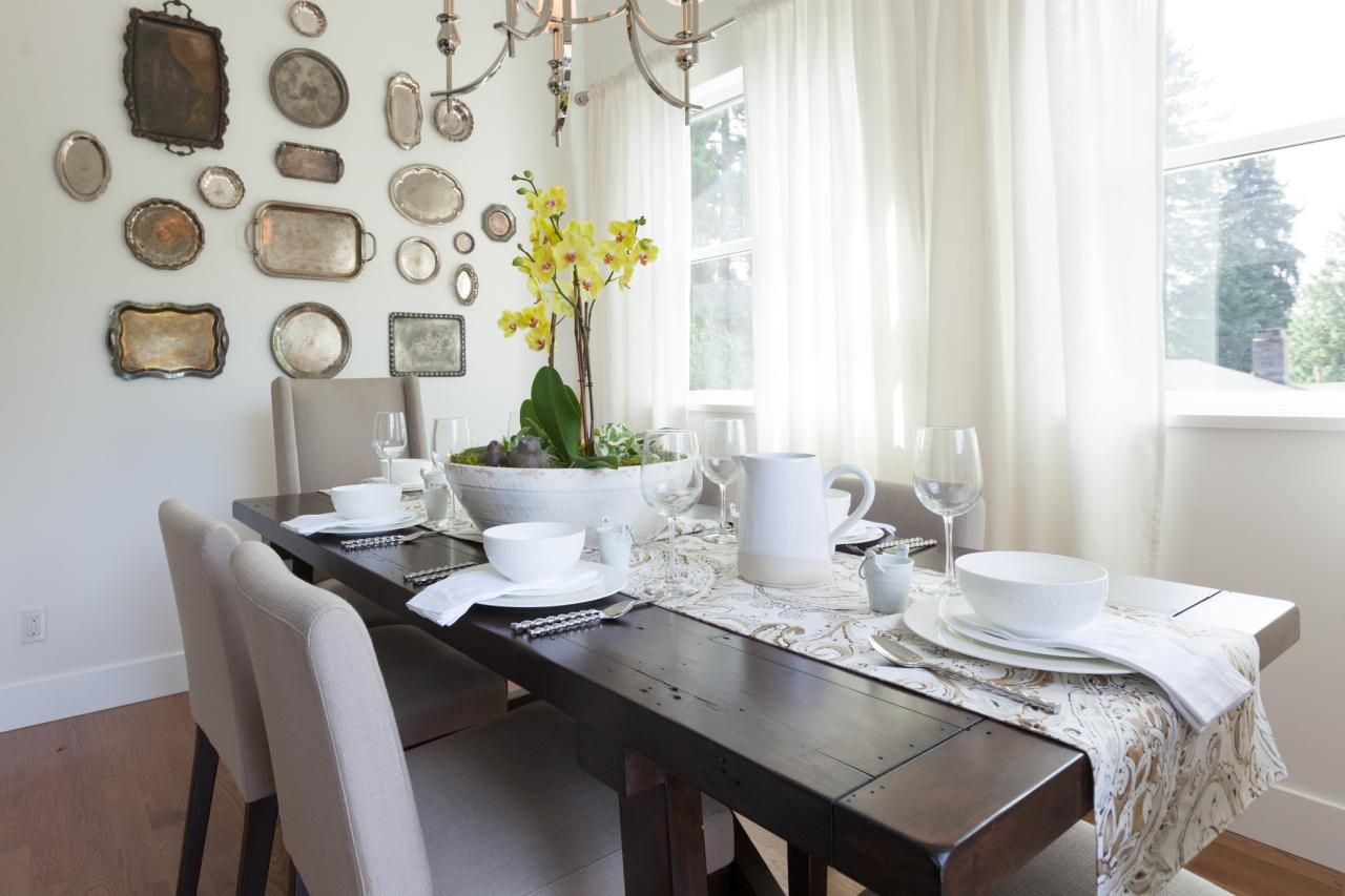As seen on Love It or List It, this beautiful, dark stained farmhouse table is the center of attention in this dining room. The light color in the space is accented by the natural light coming in through the window bank, while the antique silver serving trays give the space a vintage feel.