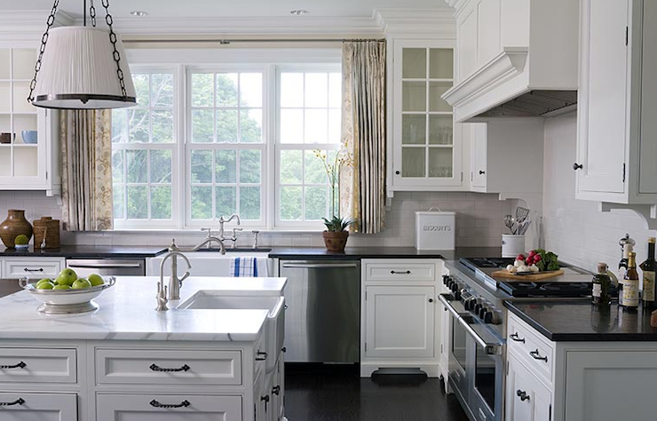 White kitchen cabinets, white carrara marble countertops, glass-front cabinets, black granite countertops, kitchen island, double dishwashers, white subway tiles backsplash and stainless steel appliances.