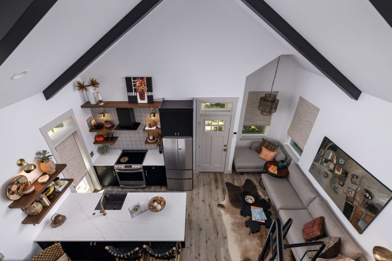 This picture shows how spacious a small home can really be! Click for a full tour of this amazing tiny home, complete with a spiral staircase and beautiful upstairs.    #tinyhome #efficienthousing #homespace #homeinspo #homelayout #interiordesign #indetailinteriors #tinyhouse #smallhomeideas #homerenovation #design #interiordecorating #originalartwork