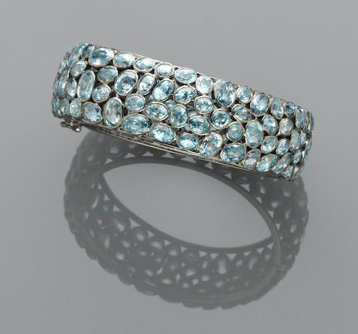 Blue Zircon Bracelet Sure to create a summery statement is this pretty hinged bangle bracelet, set with oval faceted Cambodian blue zircons in various sizes, mounted in silver, inner circumference 8in.