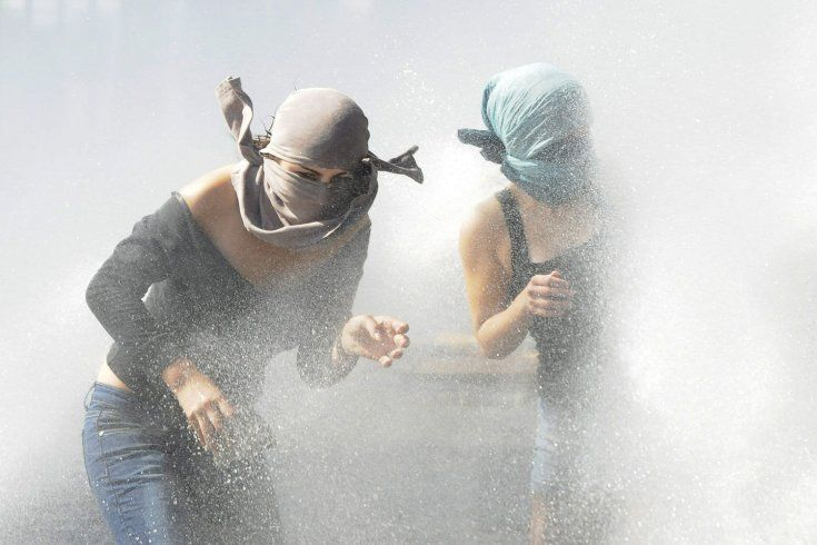 Two protesters are sprayed with water from an anti-riot vehicle at the University of Santiago de Chile, Chile.