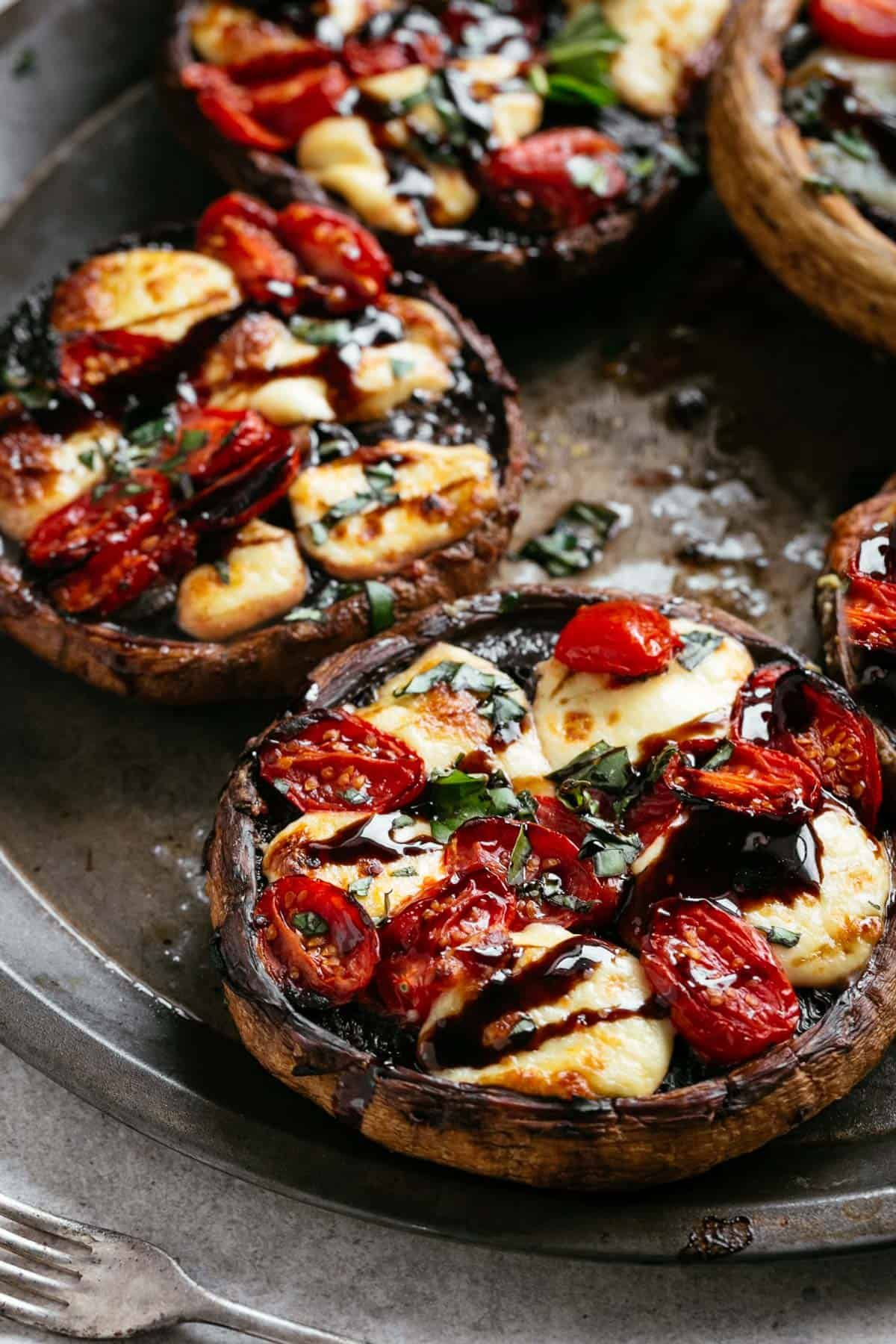 Caprese Stuffed Garlic Butter Portobellos! Garlic butter portobello mushrooms stuffed and grilled with fresh mozzarella cheese, grape tomato slices and drizzled with a rich balsamic glaze! Low carb, healthy and perfect to enjoy for lunch, dinner or as a filling snack!
