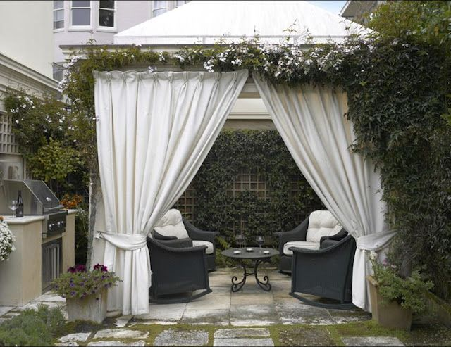 Large White Outdoor Living Area With Curtains And Vines On Pergola