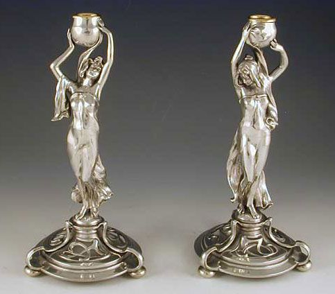A superb pair of polished pewter candlesticks in the form of Art