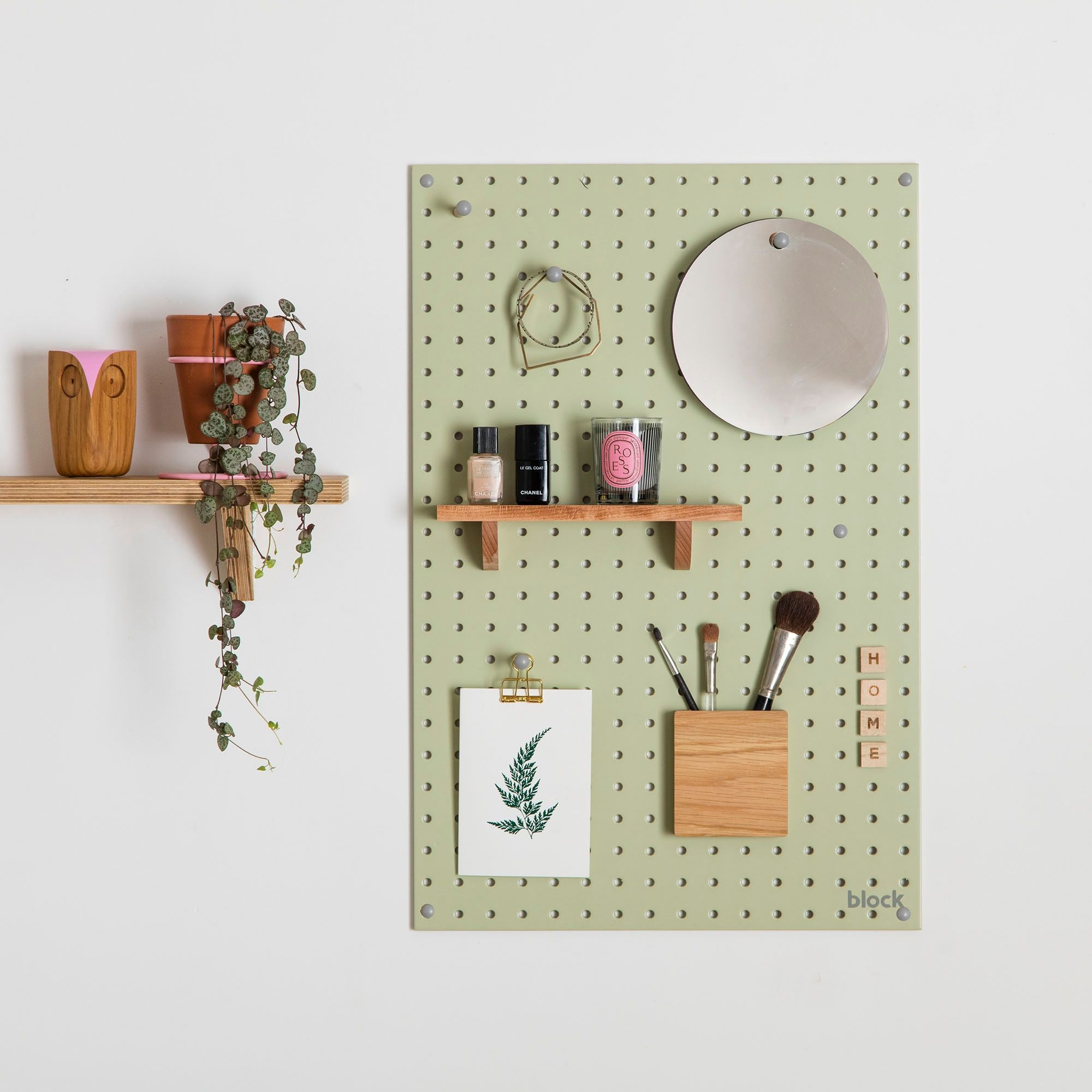 Pegboard Ideas - Green pegboard with wooden pegs