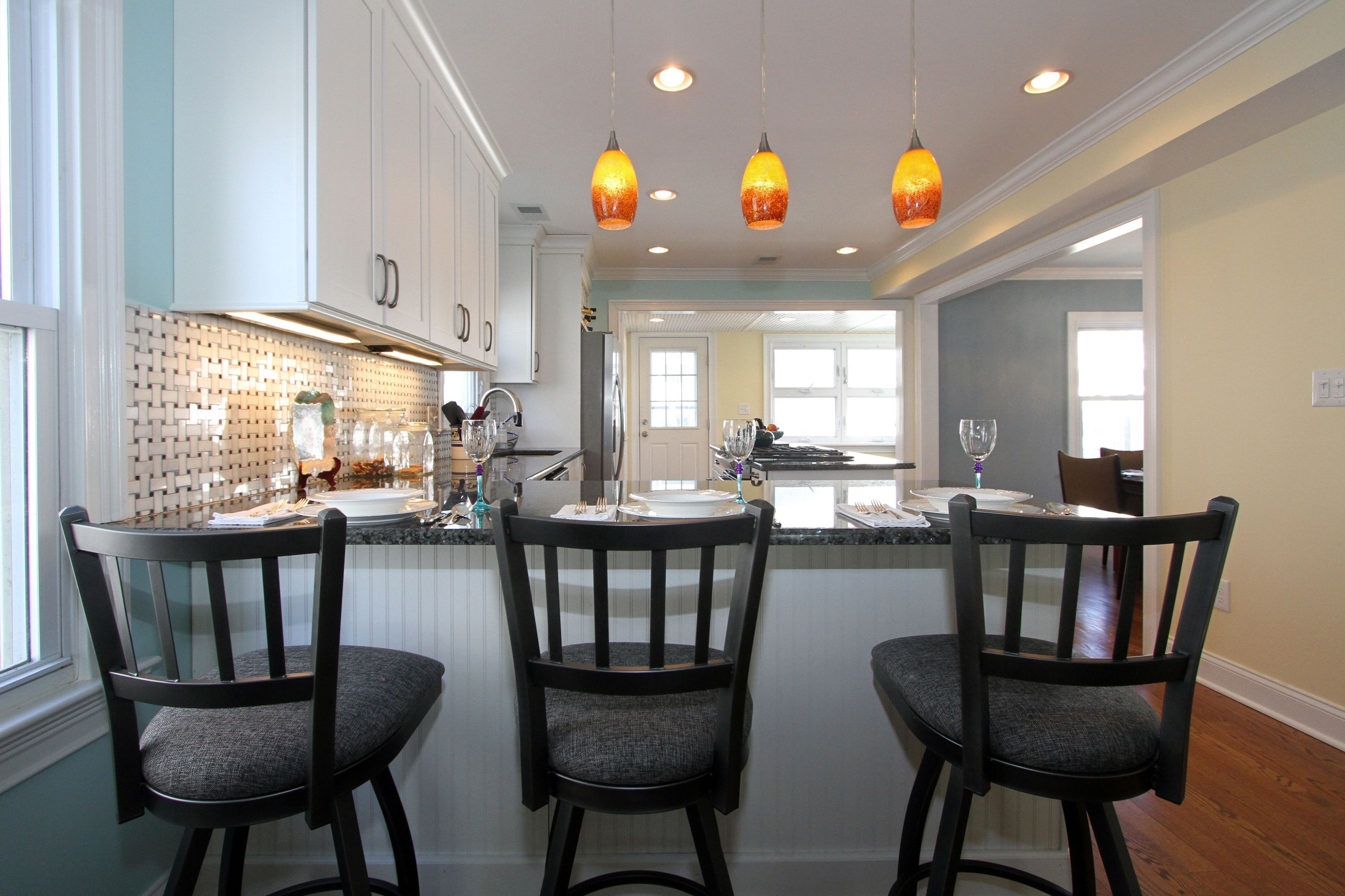 Simple White Open Kitchen With Maple Cabinets, Colorful Pendant Lights,