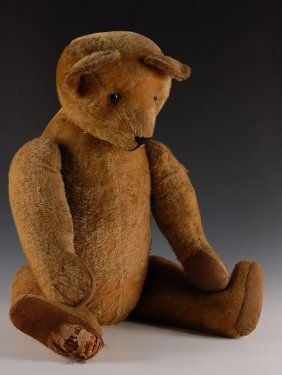 Large antique excelsior-filled bear with glass eyes and jointed arms and legs, a pronounced hump and a turning head. There is a Steiff button in the ear. Measures 36 inches.