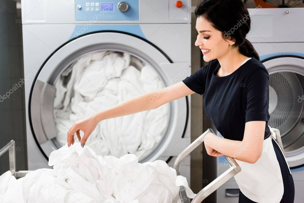 Cheerful Maid Looking Bed Sheets While Standing Washing Machines