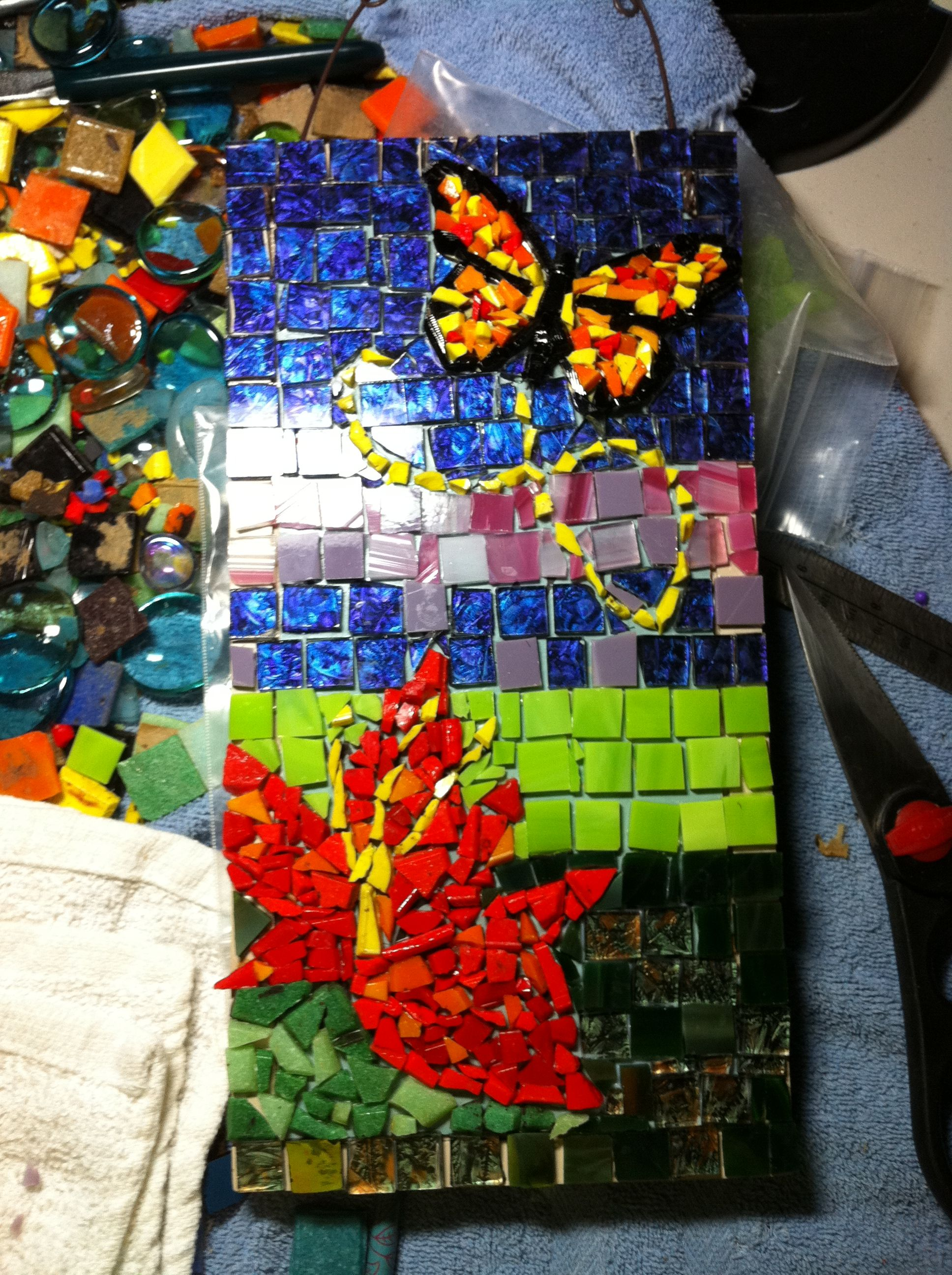 Using an Up-cycled pressed board decorative thingie, I covered it with glass then grouted. It still had the hanger so that was useful
