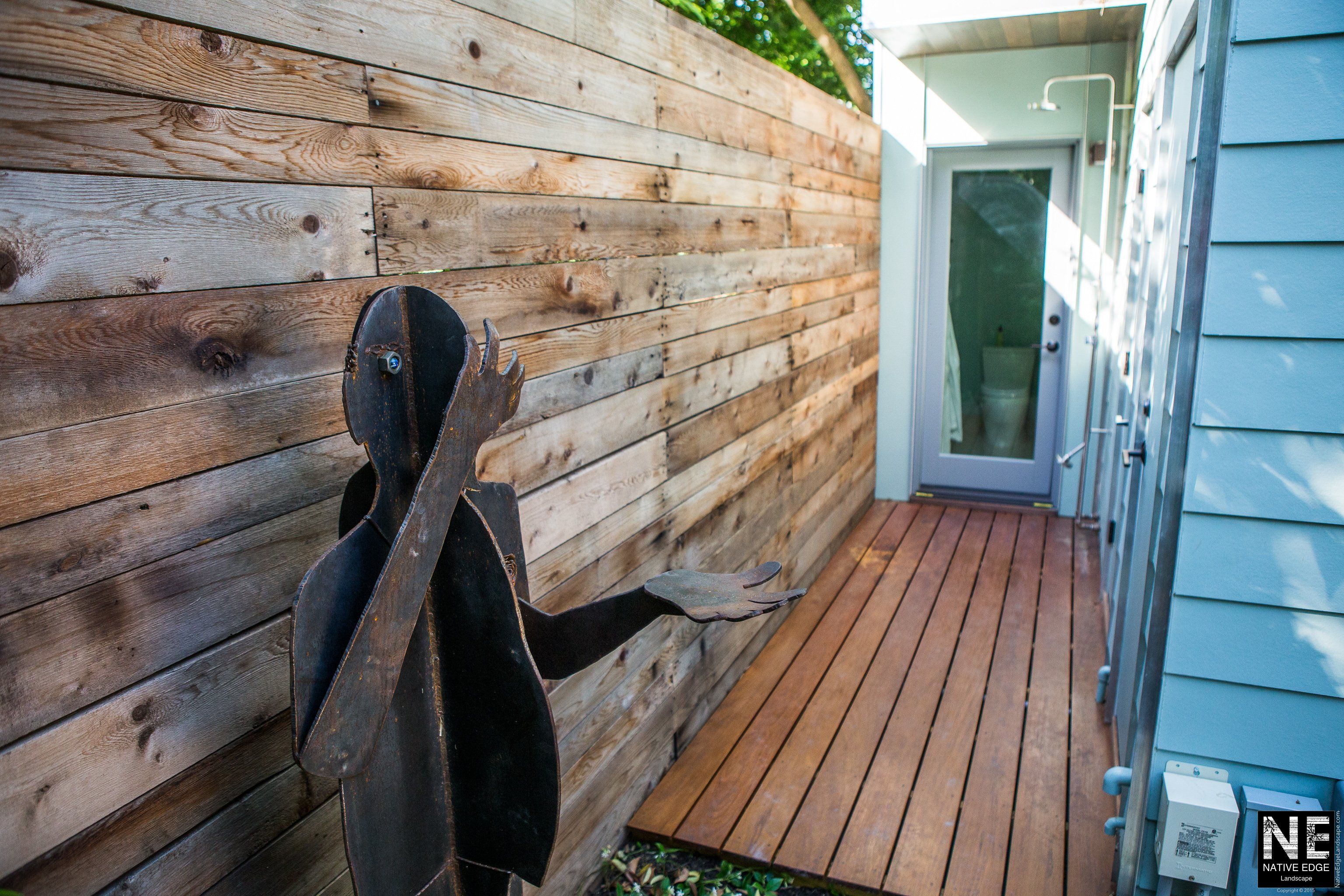 Outdoor shower area with custom iron sculpture \