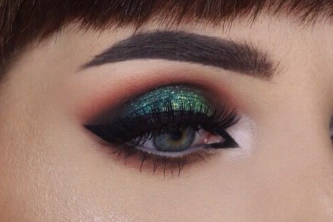 Warm toned brown smokey eyes with teal green glitter in the middle of the lids.