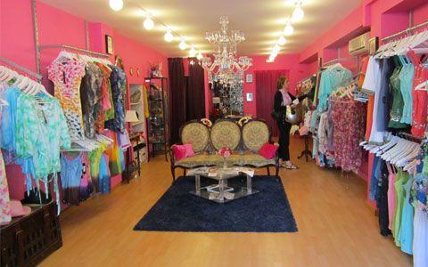 Tienda de moda de Sra. con mobiliario de la serie 4000 con cremalleras directas a pared con estantes, barras y soportes inclinados para confeccion