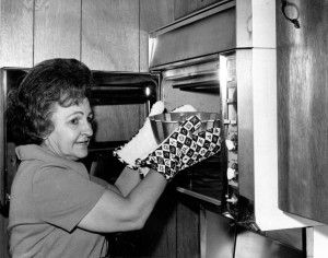 Ella Rita Helfrich, second place winner in the 1966 Pillsbury Bake-Off, places a bundt pan with her prize-winning Tunnel of Fudge cake in the oven.  Get the original recipe and learn about how it created the bundt cake phenomenon at The American Table.
