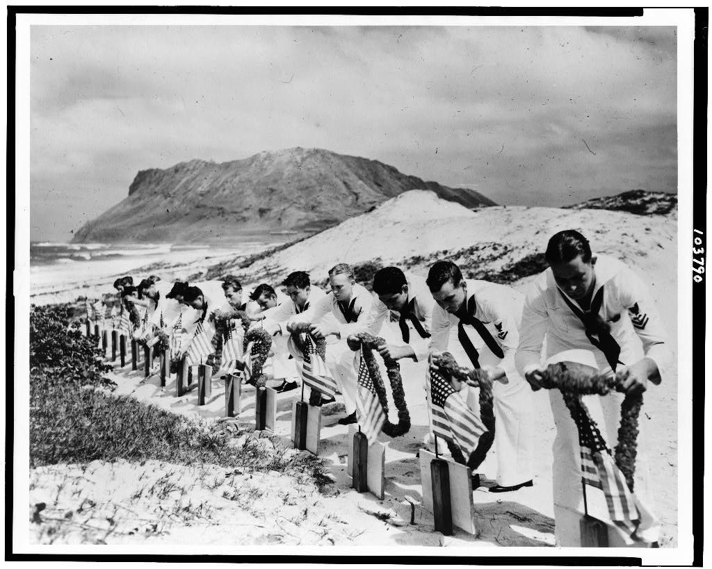 Seamen at Kaneohe Naval Air Station decorate the graves of their fellow sailors killed at Pearl Harbor, December 7, 1941