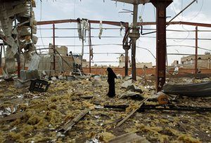 A woman inspects the damage at a factory in Sanaa, Yemen allegedly targeted by Saudi-led airstrikes