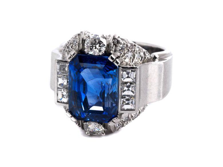 Ringweite: 54. Gewicht: ca. 15,5 g. Platin. Um 1940. Strenger Ring mit feinem Saphir im Smaragdschliff, ca. 6 ct, umrahmt von Diamanten im Prinzess- und...
