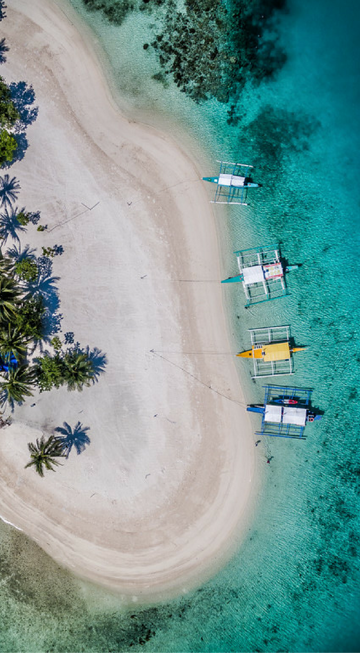 Amazing Drone photo of banca boats parked on the beach on Pass Island, Calamianes Philippines. Pass Islands is part of the Calamianes and is accessible by special request on a day trip from Coron Town. Click to see all of the Amazing Drone Photos of the Philippines by the Divergent Travelers Adventure Travel Blog at http://www.divergenttravelers.com/drone-photos-of-the-philippines/