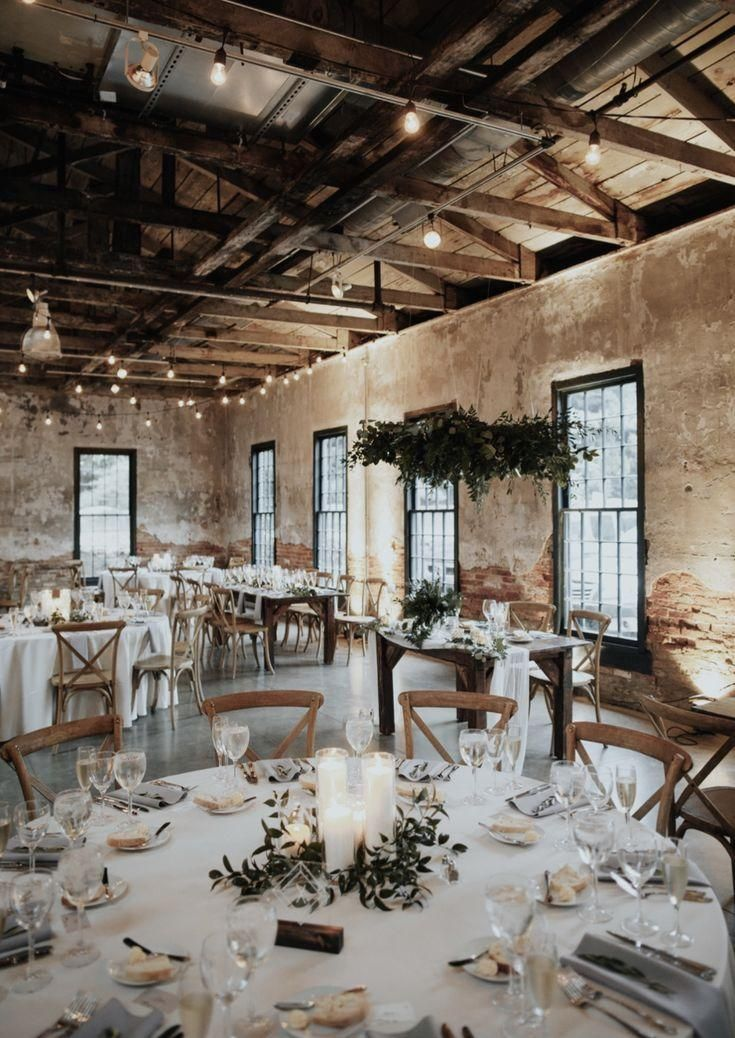 industrial bohemian wedding reception in brick building. Round tables, greenery,…