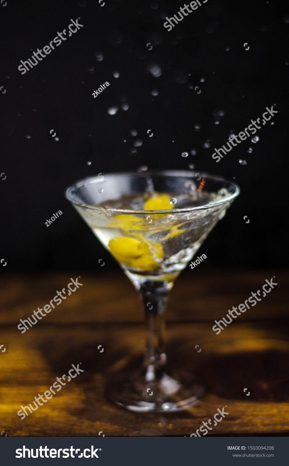 Martini glass with olive splash on dark background